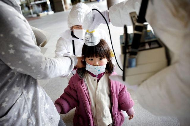 女の子の放射能を計測する防護服の大人