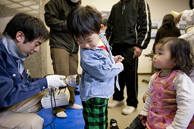 子どもを放射線測定器で検査